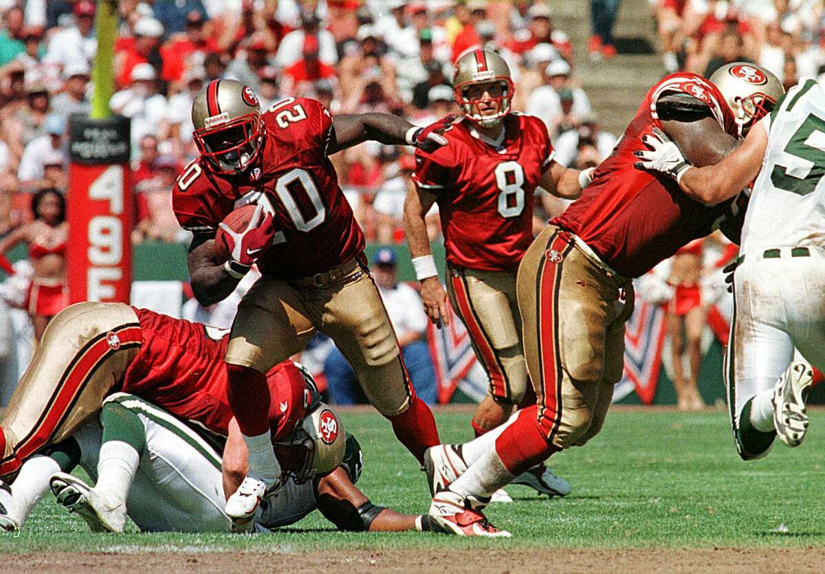 San Francisco 49ers running back Garrison Hearst (L) finds an opening after a hand-off from 49ers quarterback Steve Young (C) 06 September in San Francisco, CA. Hearst scored the winning touchdown in overtime to beat the Jets, 36-30.(Photo credit should read JOHN G. MABANGLO/AFP via Getty Images)