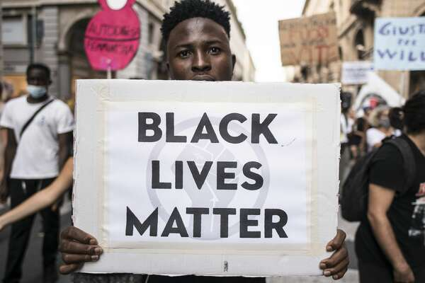 "Man with a banner reading ""Black Lives Matter"" during a protest against racism by the Black Lives Matter movement on September 13, 2020 in Turin, Italy. (Photo by Stefano Guidi/Getty Images)"