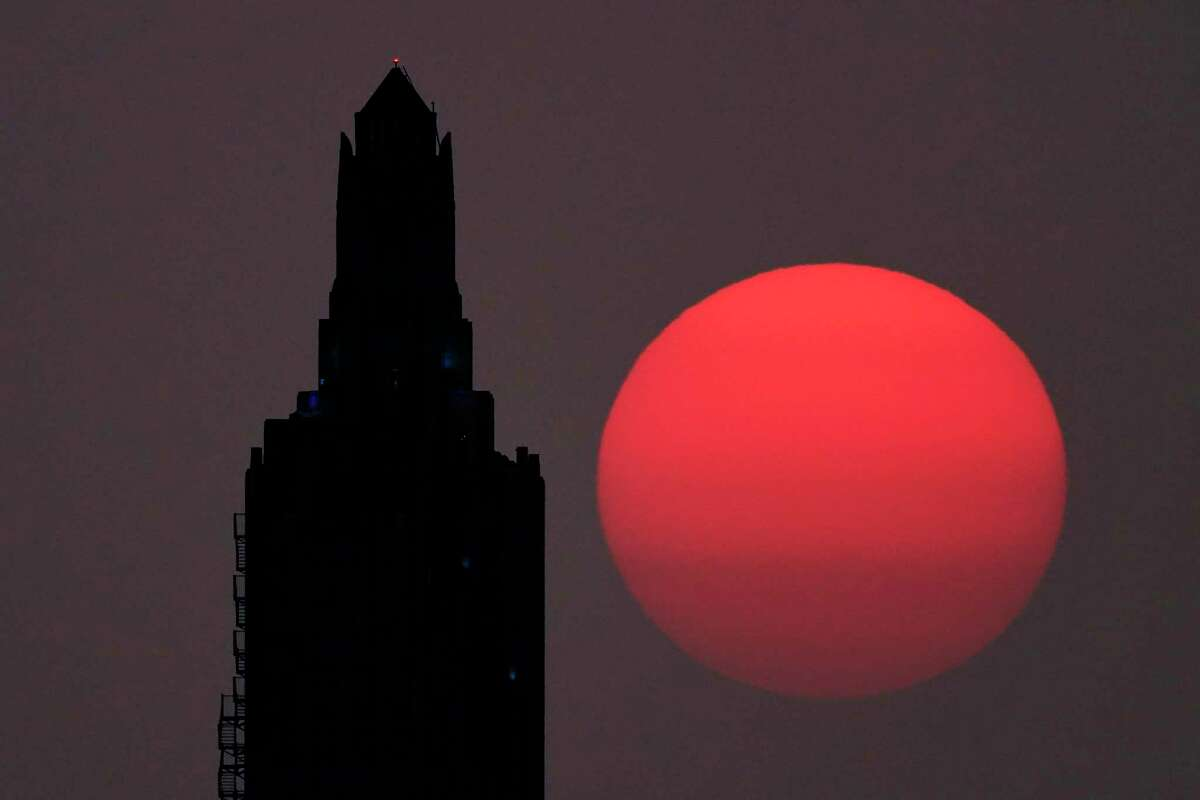 A building is silhouetted against the hazy rising sun Sept. 18 in Kansas City, Mo. Sunrises and sunsets across much of the country have been more vibrant than usual as smoke from western wildfires drift across the nation.