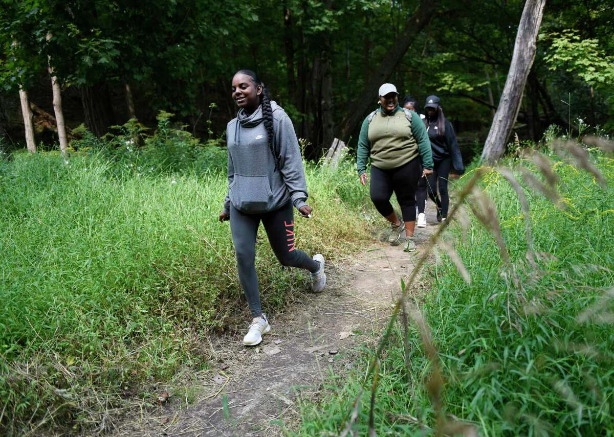 Stamford's Anyilah Middleton, left, Aliyah Burke, and others walk through the woods on a seasonally crisp day at Newman Mills Park in Stamford, Conn. Wednesday, Sept. 16, 2020. The weather is expected to remain sunny with highs between the mid-60s and mid-70s for the foreseeable future.
