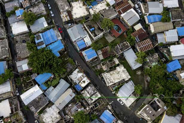 Blue tarps cover homes damaged in 2017 by Hurricane Maria in San Juan, Puerto Rico.