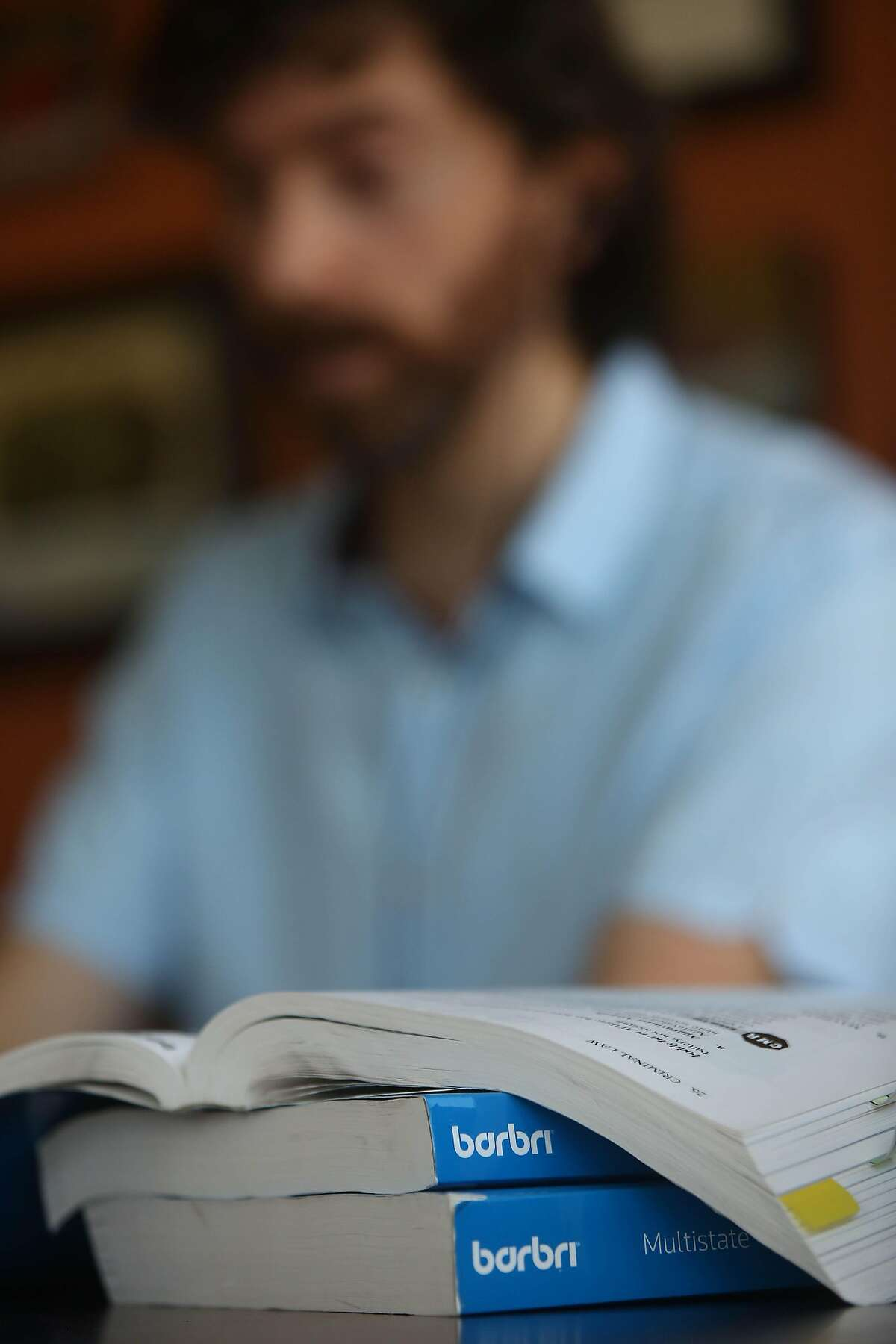 Study materials are seen next to Daniel Schweitzer, state bar tutor, as he talks to a client during a tutoring session from his home on Wednesday, September 16, 2020 in San Francisco, Calif.