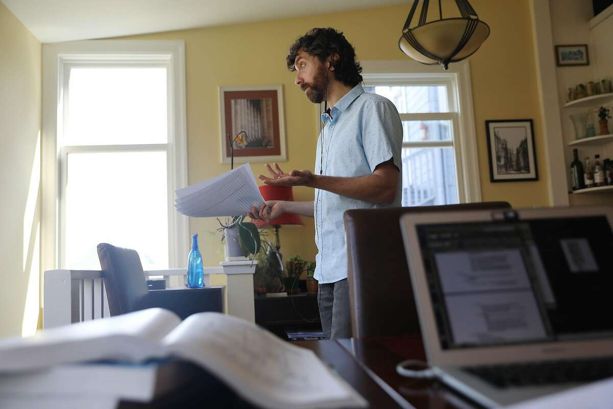 Daniel Schweitzer, state bar tutor, carries papers and gestures as he talks to a client during a tutoring session from his home on Wednesday, September 16, 2020 in San Francisco, Calif.