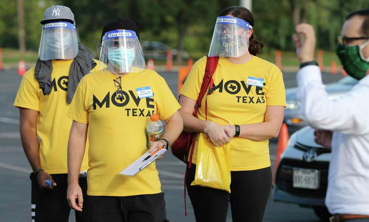 """Voter registration helpers don face shields as Spurs Sports & Entertainment and non-partisan non-profit MOVE Texas team up to help people register to vote safely, simply and swiftly as possible on Tuesday, Sept. 15, 2020. Volunteers and motorists lined up early Tuesday evening on the grounds of the AT&T Center to fill out voter registration forms. New voters remained in their cars as they spoke with volunteers who helped walk them through the voter registration process. The Spurs Coyote joined and greeted people as they filled out the paperwork. As a treat for those who came out to register, the Spurs championship trophies were on display for photographs as well as a commemorative """"Vote"""" t-shirt was available."""
