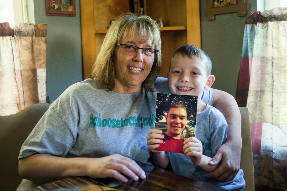 Vickey Blackwell Mishoe and her grandson, Brayden Mishoe, 5, hold a photo of Vickey's son and Brayden's father, Tyler Mishoe, who died by suicide in 2016. (Katy Kildee/kkildee@mdn.net)