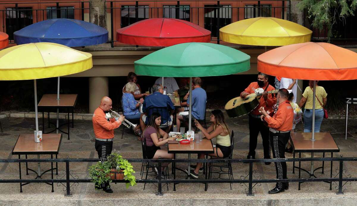 A mariachi group place for diners at a restaurant along the River Walk that has reopened in San Antonio, Monday, June 15, 2020, in San Antonio. The restaurant had been closed due to the COVID-19 pandemic. (AP Photo/Eric Gay)