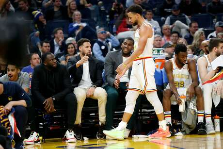 Golden State Warriors' Draymond Green, Klay Thompson and Kevon Looney greet Stephen Curry in 2nd quarter against Toronto Raptors during NBA game at Chase Center in  San Francisco, Calif., on Thursday, March 5, 2020.