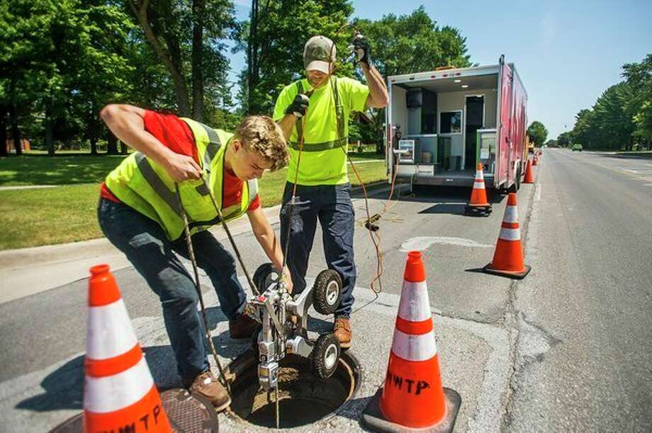 Craig Baumer, center, and Tyler Eaton, left, with the City of Midland, retrieve a robot from a storm sewer pipe underneath N. Saginaw Road after performing an inspection on Wednesday in Midland. The two work inside a portable work station as they cover one large section of pipe at a time, moving down the road as they perform inspections. (Katy Kildee/kkildee@mdn.net)