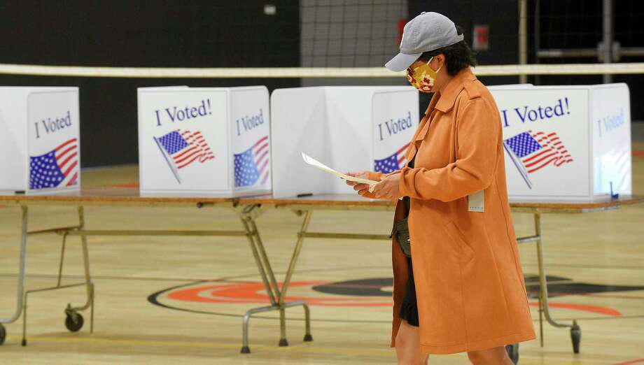 A voter prepares to cast her ballot in the presidential primary at Stamford High School in August. Stamford and many other cities and towns in the state are working with the National Guard to protect voting systems from cyber threats prior to the Nov. 3 elections. Photo: Matthew Brown / Hearst Connecticut Media / Stamford Advocate