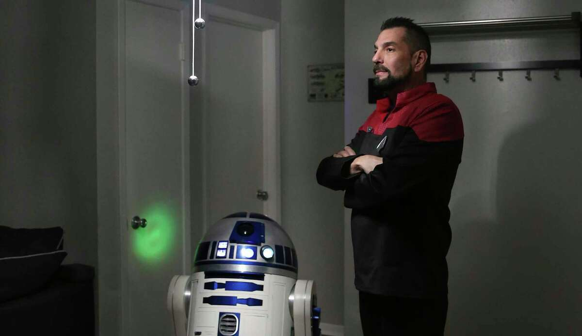 """Under the light of a Death Star light fixture, Jason Davis poses in a """"Star Trek"""" uniform with a replica he built of the """"Star Wars"""" character, R2-D2. Davis has been a fan of both franchises, but lately has favored """"Star Trek."""""""