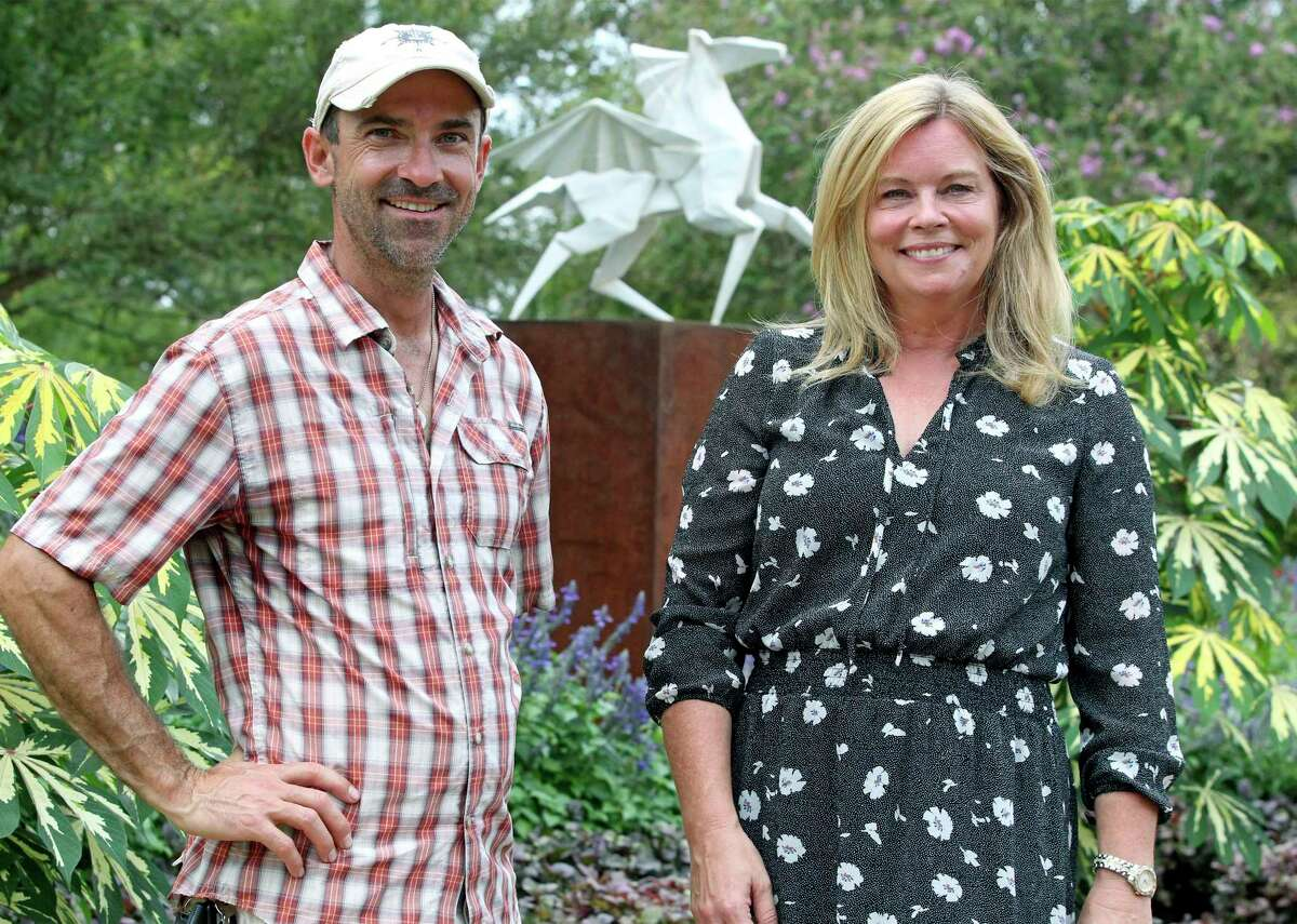 Artist Kevin Box, whose origami-inspired artwork is on display at the San Antonio Botanical Garden, stands with garden CEO Sabina Carr near a pegasus he created.