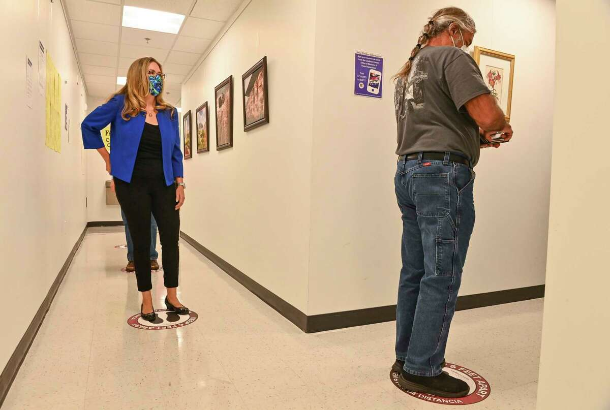 Rep. Jennifer Wexton, D-Va., center, waits to cast her vote during at the Loudoun County Office of Elections on Friday.