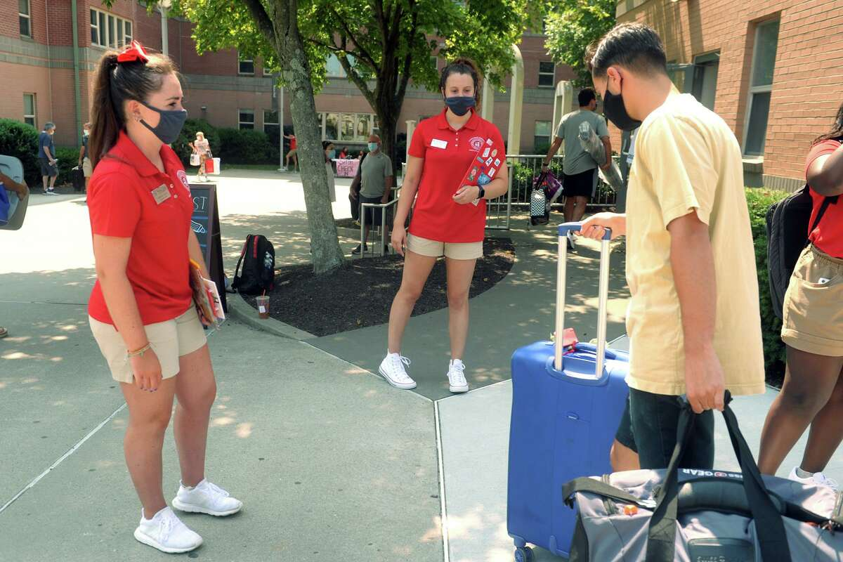 Gabriele Gately, left, a sophomore from Wantagh, NY and Catherine Rossi, a junior from Torrington, Conn. greet incoming freshmen as they arrive at their dorms on the campus of Sacred Heart University, in Fairfield, Conn. Aug. 25, 2020.