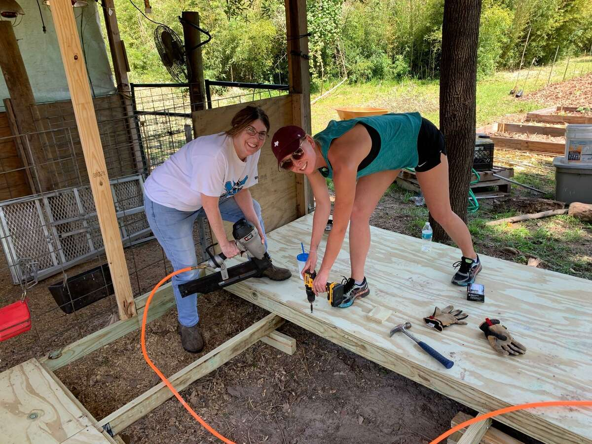 Elizabeth Hilbun, director of Living Legacy Center, left, and Britni Davison of the Rotary Club of Cypress-Fairbanks work on the tool shed in the Oasis Garden at LLC.