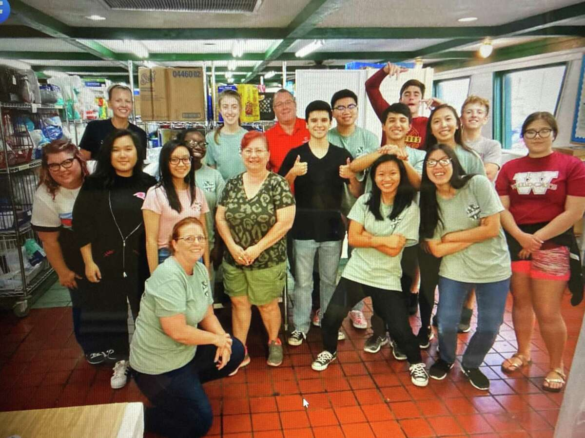 Rotarians are joined by students from Cy Woods High School Interact Program, a Rotary organization for high school students, in packing 170 carts full of groceries at CAM for distribution to the community. Pictured are Rotary members Britni Davison, Yvonne David and Curtis LaMontagne with 14 students and the director from Cy Woods High School Interact Program.