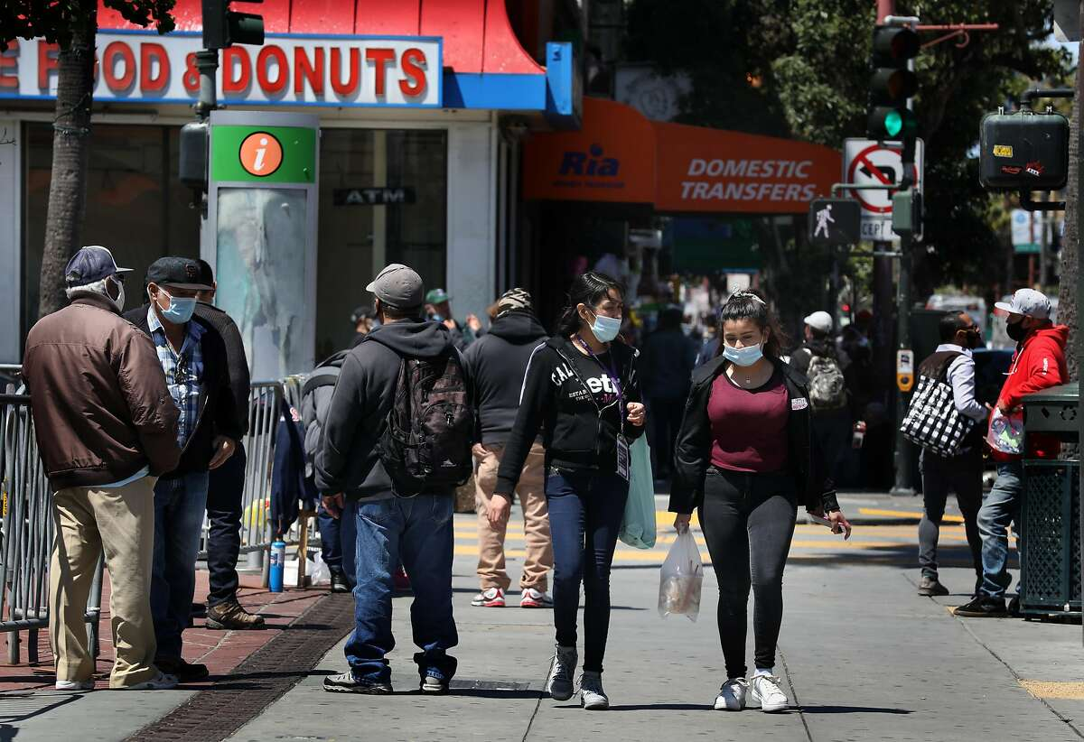 Pedestrians seen on Mission at 24th streets as businesses are re-opening in the Mission district on Tuesday, May 19, 2020, in San Francisco, Calif.
