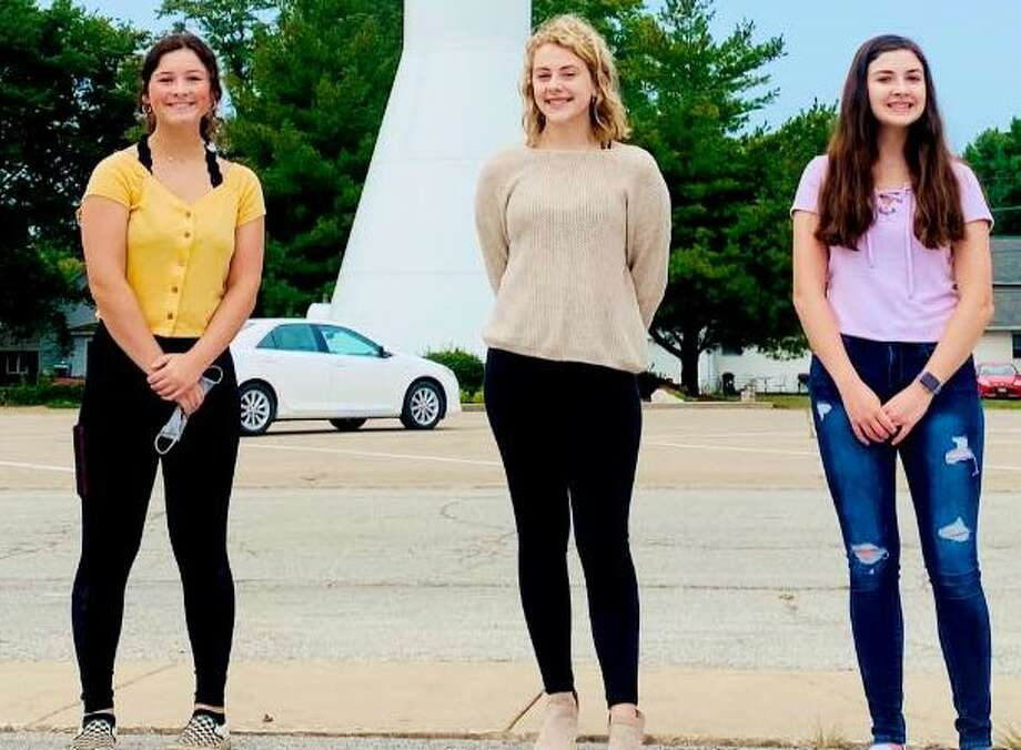 Jersey Community High School students Annie Walker (from left), Samantha Weishaupt and Morgan Margherio helped create and place downtown promotional signs in Jerseyville. Photo: Photo Provided