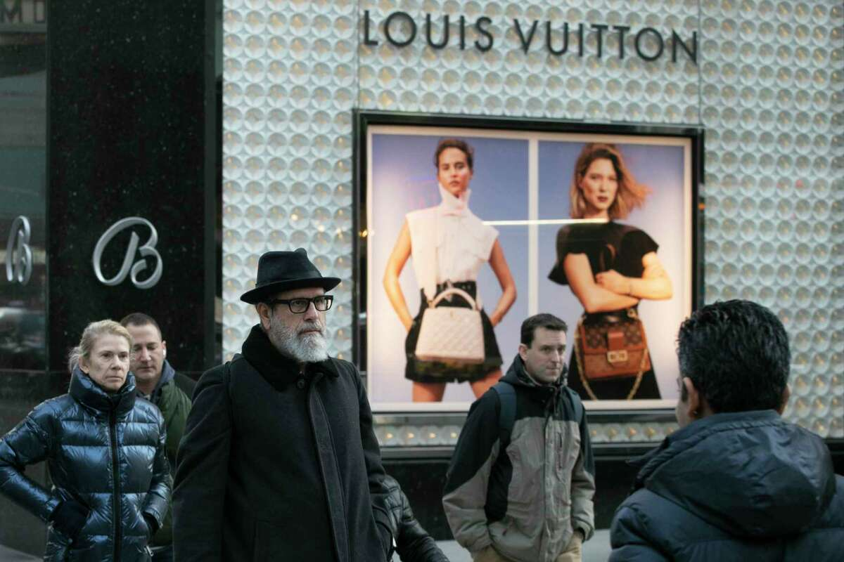 FILE - In this Nov. 25, 2019 file photo, pedestrians pass a store window for luxury brand Louis Vuitton, in New York. There are plenty of designer and luxury brands on the market, and in part because of Instagrama€™s fashion bloggers and influencers, theya€™re all the rage. Whether you want to invest in a quality item to last for years or you just want to treat yourself to a luxury label every once in a while, you can reduce your costs by shopping secondary markets or outlet stores. (AP Photo/Mark Lennihan, File)