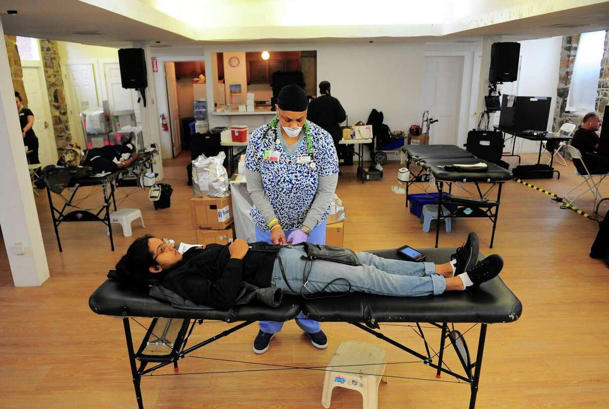 Collection Technician Tabatha Washington prepares Praveena Narayanan to donate blood during a American Red Cross blood drive at Whitneyville Cultural Commons in Hamden in April. The Red Cross is seeking volunteers to deploy to help people in need.