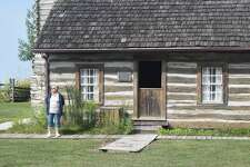 Debbie Krohe, a member of the Friends of the Rexroat Prairie, stands outside one of the cabins on the Rexroat Prairie grounds. The cabins have undergone renovation.