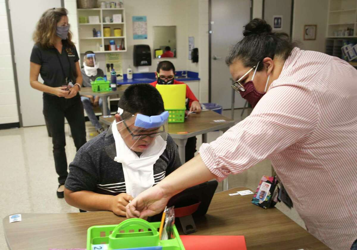 Teacher Rochelle Madrigal, right, assists Martin Casanova with logging on at the Burleson School for Innovation and Education in Edgewood ISD on Thursday.