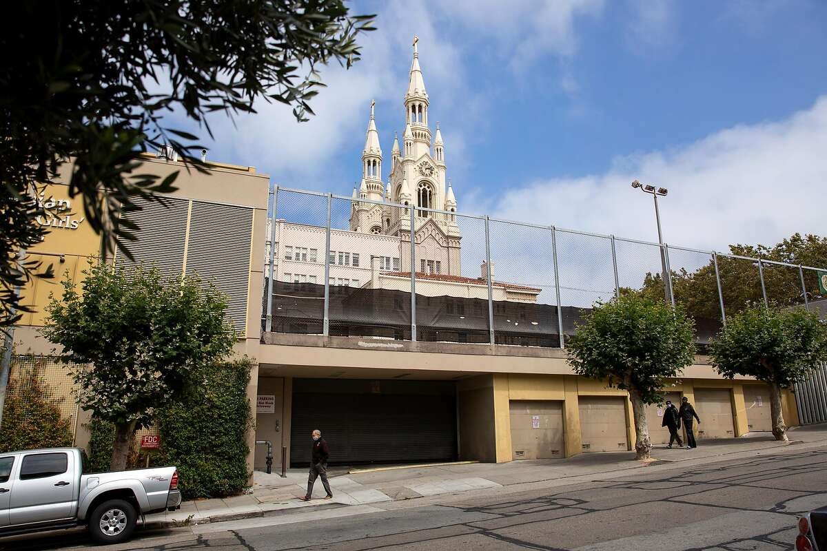 People walk past the closed gates of the parking garage for Saints Peter and Paul Church in San Francisco, Calif. on Friday, July 24, 2020.