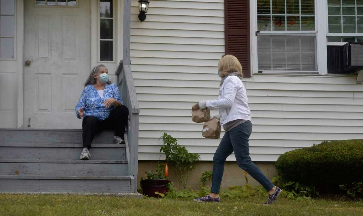 Mary Eherts, a volunteer with the New Milford Senior Center delivers meals to Carol Atwood on Wednesday morning, September 16, 2020, in New Milford, Conn.