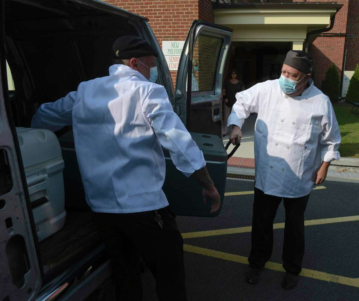 Chef Blythe Roberts, Community Culinary School of Northwest Ct, right, and Chef Jay Streck-Weller, New Milford Senior Center, load some of the 300 meals that will be delivered by the senior center on Wednesday morning. September 16, 2020, in New Milford, Conn.