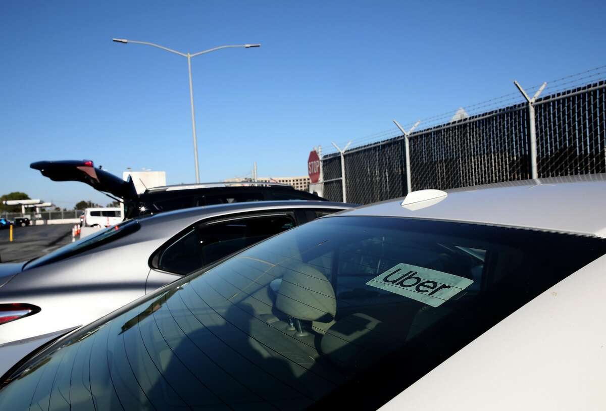 From a staging area, Uber driver Omer Iltas, 43, of San Mateo, prepares to pick up a customer at the San Francisco International Airport on Wednesday, August 12, 2020, in San Francisco, Calif. Iltas has been driving for the ride service since 2013. Uber CEO says service may have to shut down at least temporarily in California if drivers are ruled employees. It is not clear if his statement is a realistic threat or jawboning as the company continues its legal and political jousting around AB5 and Prop. 22. It also appears, at least on the surface, to contradict recent financial disclosures by the company.