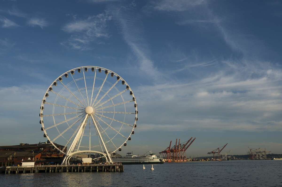 SEATTLE WATERFRONT, SEATTLE, WASHINGTON, UNITED STATES - 2012/08/05: View from Seattle Waterfront Park of the Great Wheel (Ferris wheel) at Seattle's Pier 57 with ferry in background, Washington State, USA.