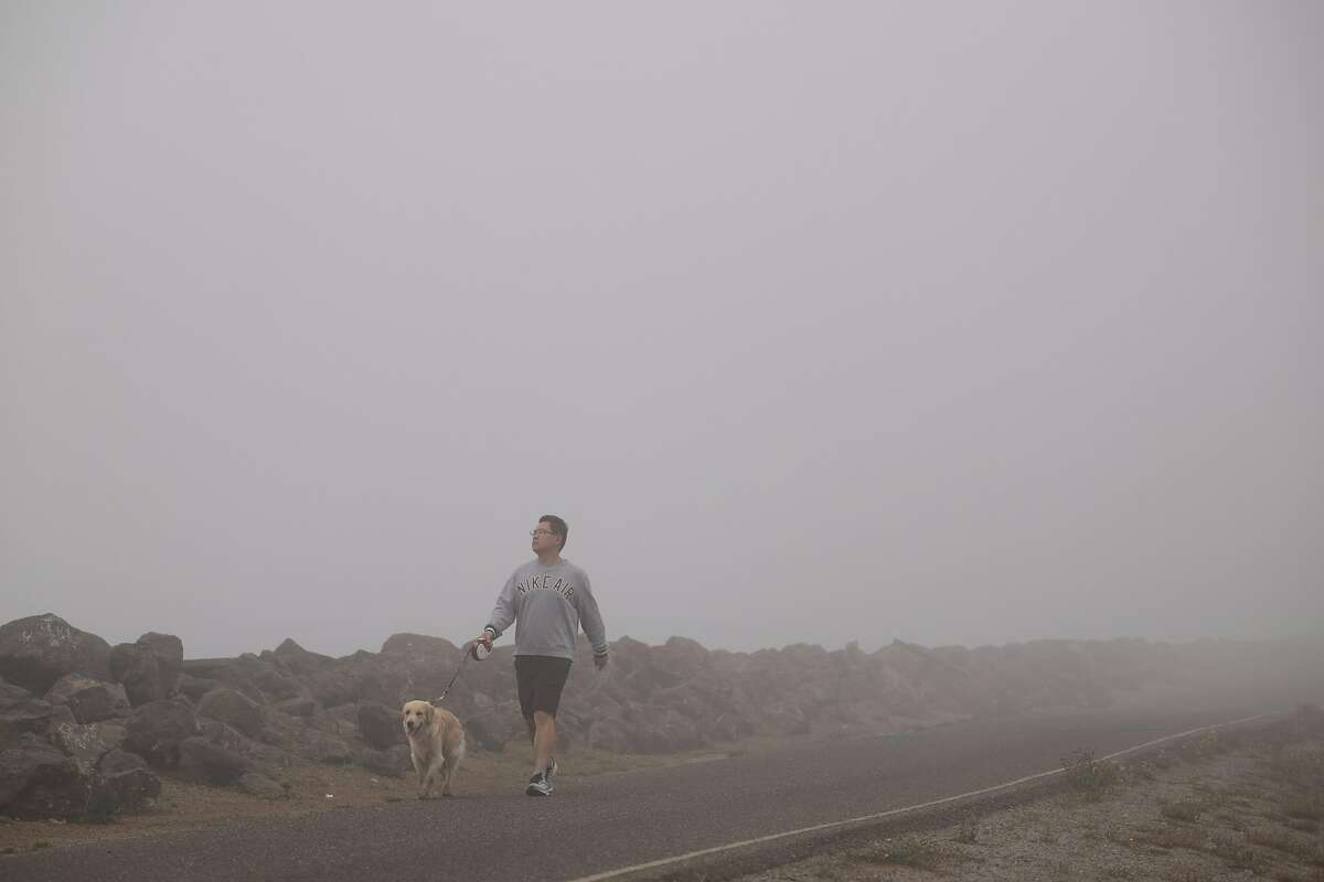 Zhen Ma walks his dog in dense smoke and fog on Treasure Island, San Francisco on Friday, September 11, 2020. San Francisco continues to experience extremely poor air quality due to the wildfires.