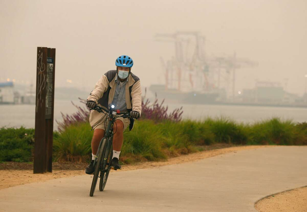 A bicyclist rides on the Bay Trail despite the smoky conditions in Oakland on Thursday, Sept. 10, 2020. Health experts strongly recommend that people not exercise outdoors on high smoke-pollution days.