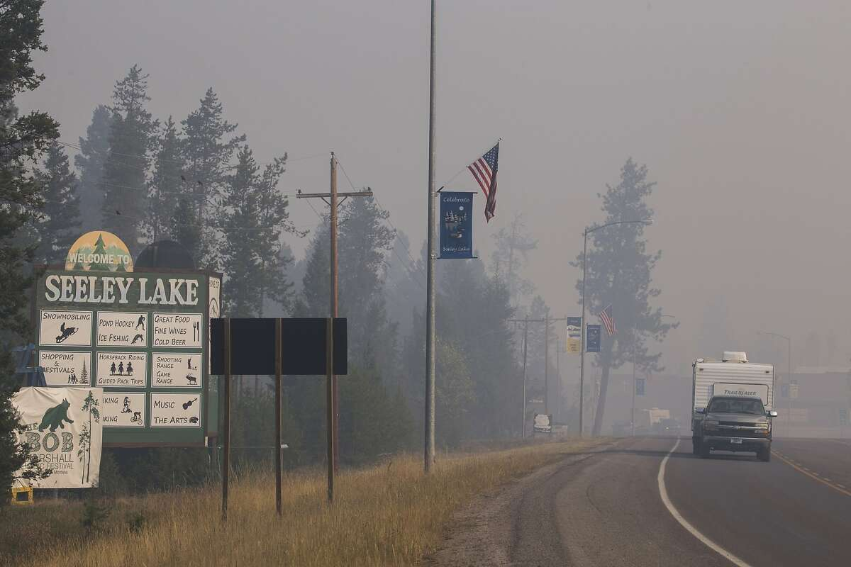 In this Aug. 10, 2017, file photo provided by the U.S. Forest Service, a pickup truck pulls a camper through the wildfire smoke in Seeley Lake in Missoula County, Mont. The small town was blanketed with hazardous smoke due to wildfires for seven weeks in 2017. A study showed residents' lung capacity declined in the first two years after the fires. The study team hasn't been able to return to Seeley Lake to check on the residents this year because of the coronavirus pandemic. (Kari Greer, U.S. Forest Service via AP, File)