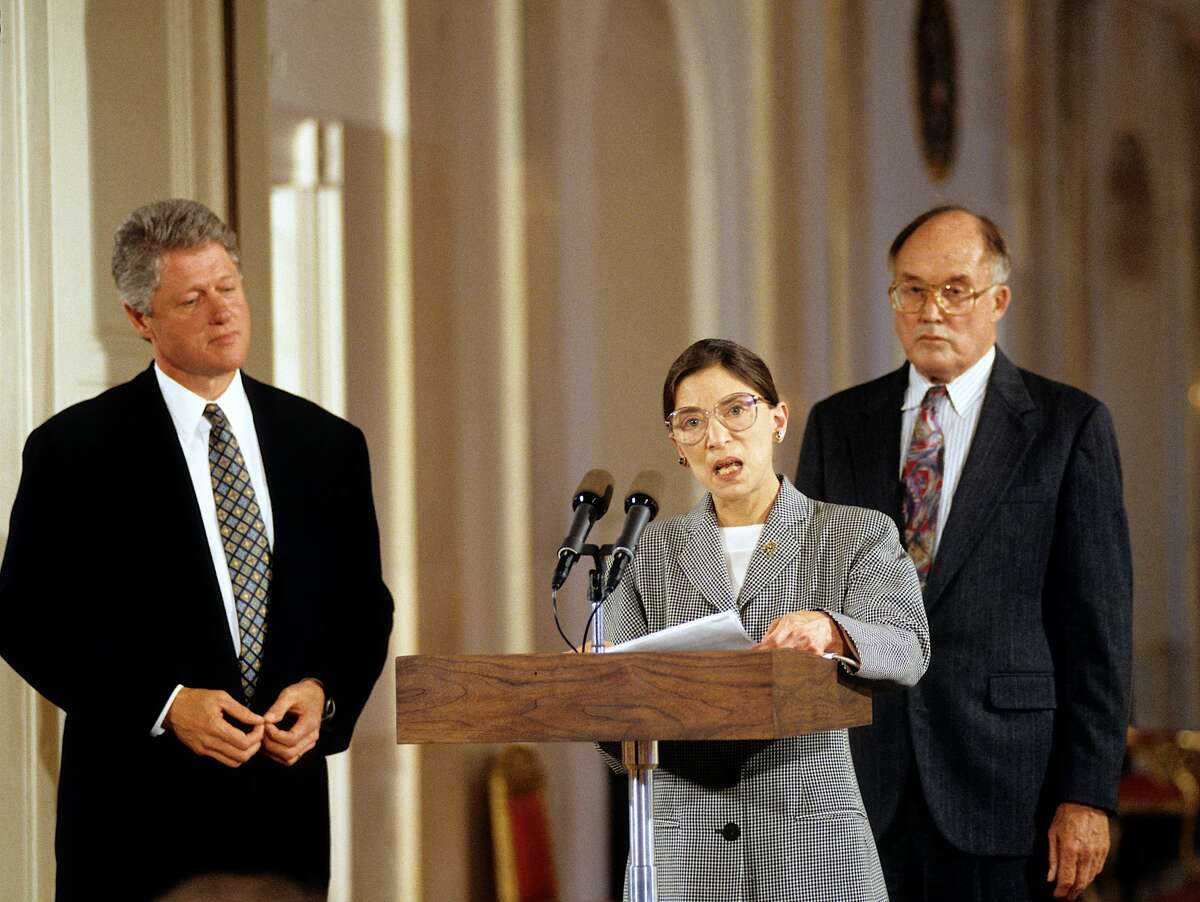 Washington DC. 8-10-1993 President William Jefferson Clinton listens to newly sworn-in Associate Justice Ruth Bader Ginsberg as she addresses members of the White House press corps in the East Room. Standing behind her is Chief Justice of the United States William Rehnquist who had just conducted the swearing-in oath of office to Justice Ginsberg. Credit: Mark Reinstein (Photo by Mark Reinstein/Corbis via Getty Images)