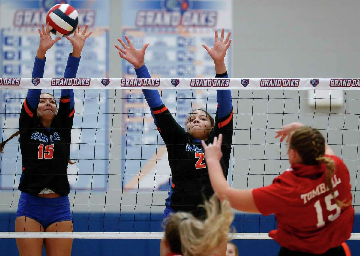 Grand Oaks outside hitter Aidan Ballard (15) blocks a shot from Tomball right side hitter Kayla Schorlemmer (15) during the first set of a non-district high school volleyball match at Grand Oaks High School, Friday, Sept. 18, 2020, in Spring.