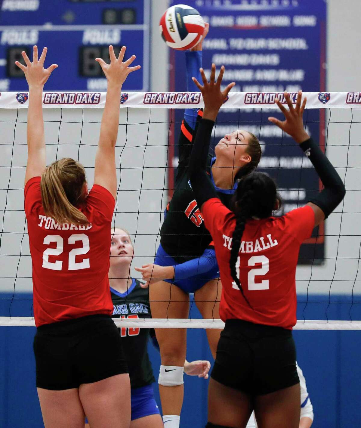 Grand Oaks outside hitter Aidan Ballard (15) gets a shot past Tomball outside hitter Faith Sabatier (22) and middle blocker Aleka Darko (12) during the first set of a non-district high school volleyball match at Grand Oaks High School, Friday, Sept. 18, 2020, in Spring.