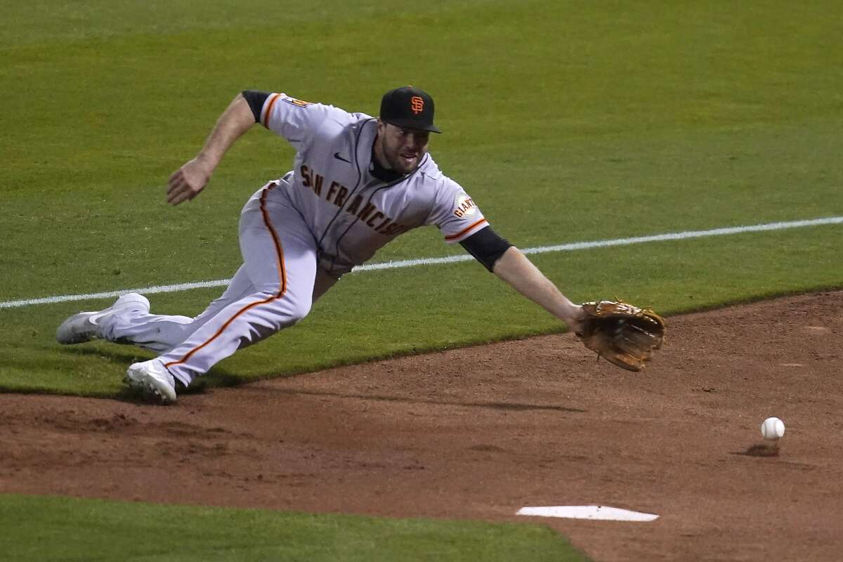 San Francisco Giants right fielder Darin Ruf dives for a foul ball hit by the Oakland Athletics' Marcus Semien during the third inning of a baseball game Friday, Sept. 18, 2020, in Oakland, Calif. (AP Photo/Eric Risberg)