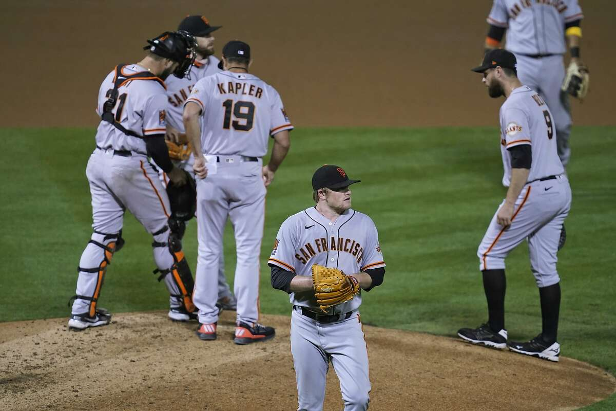 San Francisco Giants starting pitcher Logan Webb walks back to the dugout after being removed by manager Gabe Kapler (19) in the fourth inning of the team's baseball game against the Oakland Athletics on Friday, Sept. 18, 2020, in Oakland, Calif. (AP Photo/Eric Risberg)