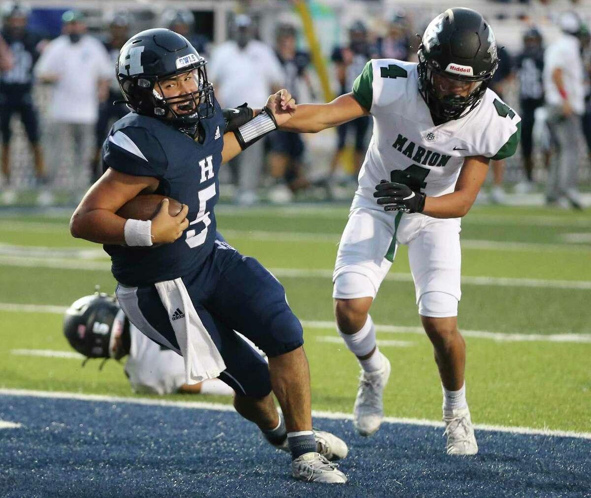 Hondo quarterback Brandon Garcia (05) scores on a three-yard keeper against Marion's Dominic Castellanos (04) during their high school football game in Hondo, Texas on Friday, Sept. 18, 2020.