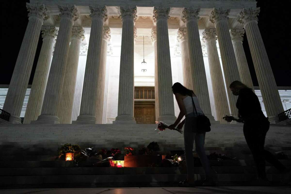 """People leave flowers in a makeshift memorial on the steps of the Supreme Court buidling in memory of late Justice Ruth Bather Ginsburg, in Washington, DC, on September 18, 2020. - Progressive icon and doyenne of the US Supreme Court, Ruth Bader Ginsburg, has died at the age of 87 after a battle with pancreatic cancer, the court announced on September 18, 2020. Ginsburg, affectionately known as the Notorious RBG, passed away """"this evening surrounded by her family at her home in Washington, DC,"""" the court said in a statement. (Photo by ALEX EDELMAN / AFP) (Photo by ALEX EDELMAN/AFP via Getty Images)"""