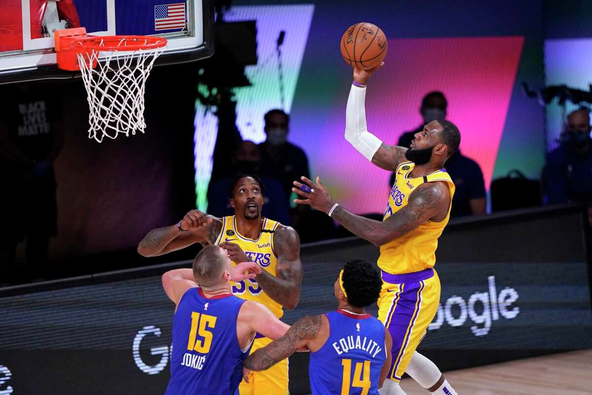 Los Angeles Lakers forward LeBron James, right, goes up for a shot as Denver Nuggets' Nikola Jokic (15), Gary Harris (14) and Dwight Howard, rear, look on during the first half an NBA conference final playoff basketball game Friday, Sept. 18, 2020, in Lake Buena Vista, Fla. (AP Photo/Mark J. Terrill)