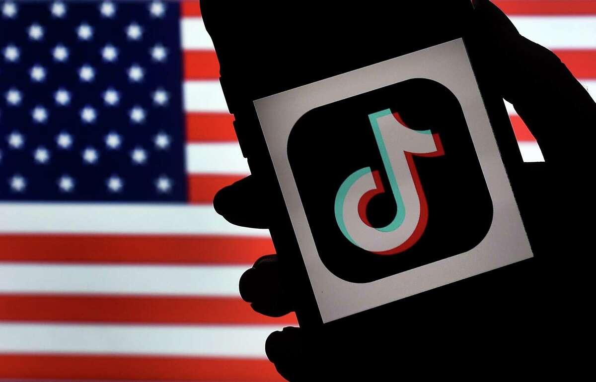 En esta fotografía tomada el 3 de agosto de 2020, el logotipo de la aplicación de redes sociales, TikTok, se muestra en la pantalla de un iPhone en una bandera de EE. UU. El 18 de septiembre de 2020, funcionarios estadounidenses ordenaron la prohibición de las descargas de las populares aplicaciones móviles de propiedad china WeChat y TikTok a partir del 20 de septiembre, diciendo que amenazan la seguridad nacional. La medida se produce en medio de las crecientes tensiones entre Estados Unidos y China por la tecnología y un esfuerzo de la administración Trump para diseñar una venta de la aplicación de video TikTok a inversores estadounidenses.