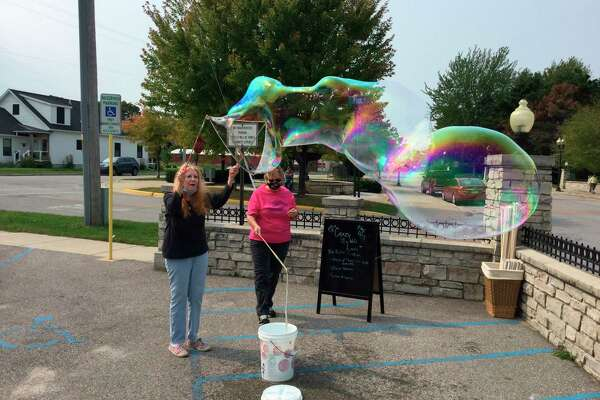 Patricia plays with bubbles while the Crazy Bubble Lady looks on, during the day-long celebration of seniors on Wednesday. (Courtesy Photo)