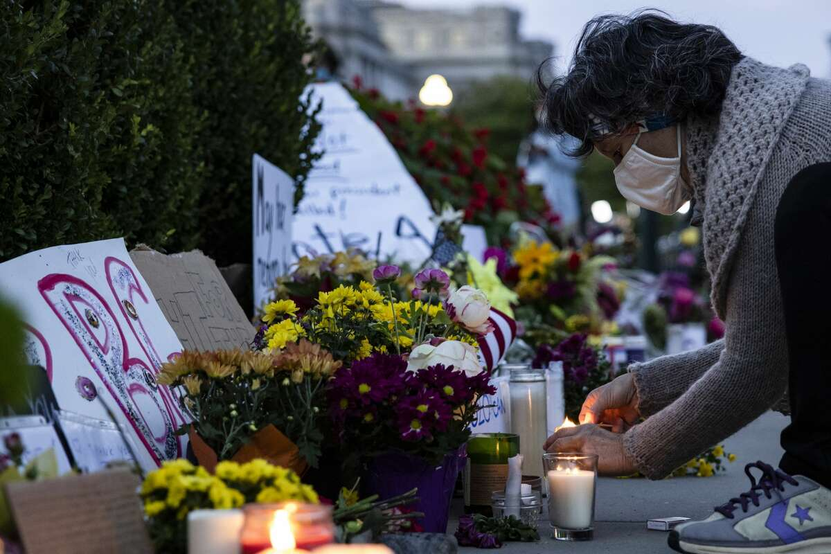 A woman lights candles in front of the US Supreme Court in honor of Supreme Court Justice Ruth Bader Ginsburg on September 19, 2020 in Washington, DC. Justice Ginsburg has died at age 87 after a battle with pancreatic cancer. (Photo by Samuel Corum/Getty Images)