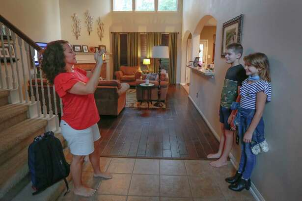 Stacey Stidham takes a photo of her children seventh-grade, Joseph and fifth-grade, Allie before the youngest head to her first day of classes Aug. 24 in Humble.