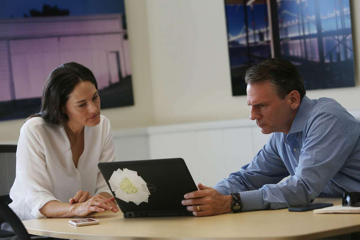 Alastair Mactaggart (right) and wife Celine Mactaggart talk as they pass a laptop between them while discussing work at their Oakland office on Friday September 18, 2020 in Oakland, Calif.