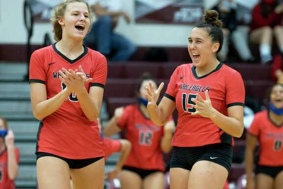 Oak Ridge right side hitter Tory Perduk (10) and setter Piper Boydstun (15) react after winning the fourth set of a non-district volleyball match at Magnolia High School, Saturday, Sept. 19, 2020.