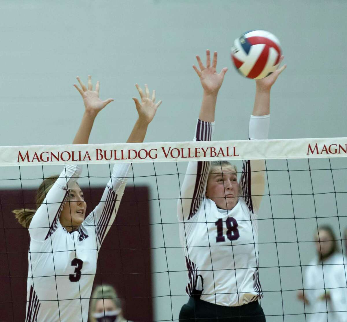 Magnolia middle blocker Reina King (3) and middle blocker Brynn Botkin (18) block a serve during the second set of a non-district volleyball match against Oak Ridge at Magnolia High School, Saturday, Sept. 19, 2020.
