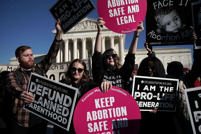 WASHINGTON, DC - JANUARY 19: Pro-life activists try to block the signs of pro-choice activists in front of the the U.S. Supreme Court during the 2018 March for Life January 19, 2018 in Washington, DC. Activists gathered in the nation's capital for the an