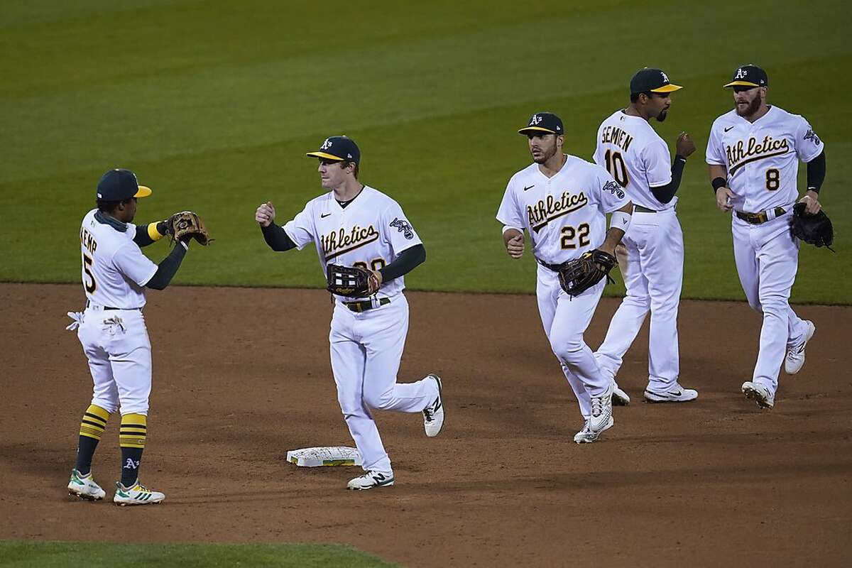 Oakland Athletics' Tony Kemp, Mark Canha, Ramon Laureano, Marcus Semien and Robbie Grossman, from left, greet each other at the end of a baseball game against the San Francisco Giants on Friday, Sept. 18, 2020, in Oakland, Calif. Oakland won 6-0. (AP Photo/Eric Risberg)